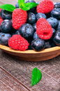 Raspberry and blueberry background of with a sprig of mint Stock Photo