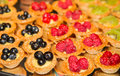 Raspberry blueberry and kiwi tarts many individual fruit on a buffet Stock Photography