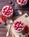 Raspberry dessert, cheesecake, trifle, mouse in a glass on a wooden background. Top view Royalty Free Stock Photo