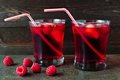 Raspberry fruit drinks with bendy straws over a dark background Royalty Free Stock Photo