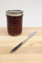 Raspberry jam jar of on a cutting board with a knife Royalty Free Stock Images