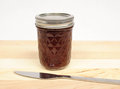 Raspberry jam jar of on a cutting board with a knife Royalty Free Stock Photo