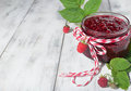Raspberry jam in a jar on the wooden table and fresh berries light background Stock Photography