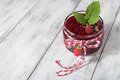 Raspberry jam in a jar on the wooden table and fresh berries light background Stock Photo