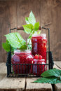 Raspberry jam in a jars and leaves on the wooden background Stock Photo