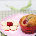 Raspberry muffin square shot of and white chocolate on pink plate white chocolate melts and in the foreground Stock Photo