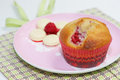 Raspberry muffin and white chocolate on pink plate white chocolate melts in the background Royalty Free Stock Image
