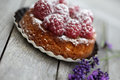 Raspberry tarte small french with icing sugar on wooden table Royalty Free Stock Image