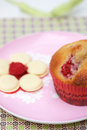Raspberry and white chocolate muffin closeup shot of on pink plate melts in the foreground Royalty Free Stock Photo