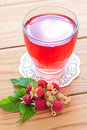 Raspberry and white currants compote in the glass on the wooden table Royalty Free Stock Images
