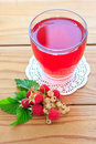 Raspberry and white currants compote in the glass on the wooden table Royalty Free Stock Photos