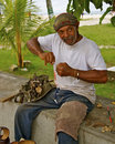 Rastaman san andres island colombia making ethnic jewelry with black corals at beach Royalty Free Stock Photo