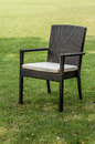 Rattan chair with cushion in the garden Royalty Free Stock Photo