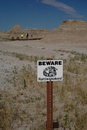 Rattlesnakes warning sign this alerts tourists to potential dangers of snakes lurking beneath rocks in badlands national park Royalty Free Stock Images
