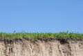 Ravine or gully cut with soil grass and blue sky Stock Photography