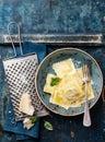 Ravioli pasta with parmesan mozzarella cheese basil and on blue background Stock Photo