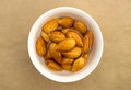 Raw almonds soaking in a white bowl of water against brown background Royalty Free Stock Image