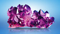Raw amethysts crystals of amethyst on blue background Royalty Free Stock Image