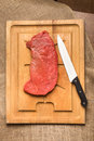 Raw beef steak on cutting board with knife Stock Photo