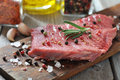Raw beef steak with spices and rosemary on wooden background Stock Photos