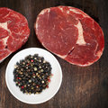 Raw beef steaks with peppercorns on wooden board Royalty Free Stock Image