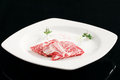 Raw beefsteak on a white plate black background photo it in the studio slice of with Royalty Free Stock Images