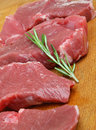 Raw boneless lamb leg meat steaks on wooden chopping board Stock Images