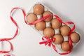 Raw brown eggs in an egg carton with red polka dot ribbon and bow on white background. Top view Royalty Free Stock Photo