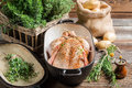 Raw chicken with herbs in casserole dish closeup of on old wooden table Royalty Free Stock Photography