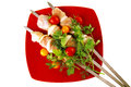 Raw chicken kebabs on red served with tomatoes Stock Photo
