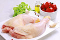 Raw chicken legs decorated with salad olive oil and cherry tomatoes on white plate diet food healthy lifestyle Stock Photo