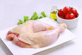 Raw chicken legs decorated with salad olive oil and cherry tomatoes on white plate diet food healthy lifestyle Stock Photos