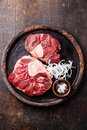 Raw cross cut veal shank for making osso buco fresh and ingredients on dark wooden background Royalty Free Stock Photo
