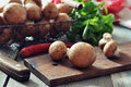 Raw dirty champignon on wooden cutting board with pepper and knife Royalty Free Stock Photos