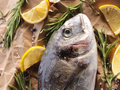 Raw dorado fish with rosemary and sea salt server on old wooden table Stock Photo
