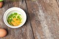 Raw egg in a bowl selective focus and onion on wooden table, Top Royalty Free Stock Photo