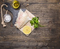 Raw fish fillet on a cutting board with lemon, herbs, butter and salt border ,place for text wooden rustic background top view
