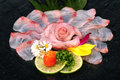 Raw fish in rose form tai usuzukuri with tomato and lime decorate mangrove jack Royalty Free Stock Images
