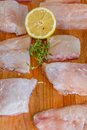 Raw fish slices with lemon on wooden cutting board