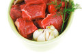 Raw fresh beef meat slices in a ceramic dish with onion and red peppers isolated over white backkground Stock Photo