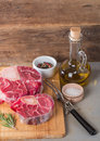 Raw fresh cross cut veal shank and seasonings for making osso buco on wooden background Royalty Free Stock Image
