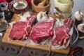 Raw fresh meat rib eye steak composition on wooden background