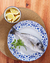 Raw gilt head bream on a dish with lemon and parsley Royalty Free Stock Images