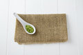 Raw green lentils white ceramic spoon sitting burlap white wooden boards Stock Image