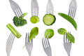 Raw green vegetables on forks isolated against white background Stock Photo