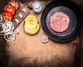 Raw Ground beef meat Burger steak cutlets in pan with vegetables, spices border ,with text area  wooden rustic background top vi Royalty Free Stock Photo