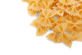 Raw and hard farfalle pasta, on a white background. Tasty traditional farfalle Italian macaroni. Flour products, top view