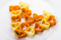 Raw heart shaped pasta on white plate Stock Photos