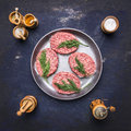 Raw homemade burgers Beef, lined inside vintage pan with spices and herbs on  blue rustic wooden background top view Royalty Free Stock Photo