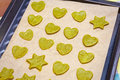 Raw homemade cookies with green tea matcha in star shape and heart shape on baking sheet